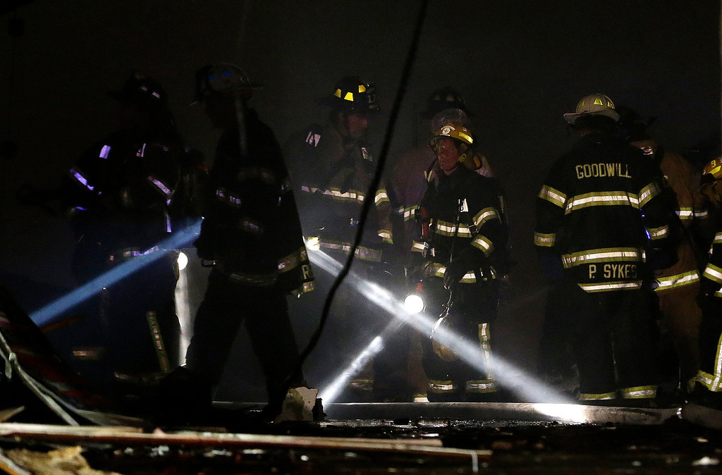 . Firefighters use flashlights while checking an area where they fought off flames during a massive fire at the Seaside Park boardwalk, Thursday, Sept. 12, 2013, in Seaside Park, N.J. The fire, which apparently started in an ice cream shop and spread several blocks, hit the recently repaired boardwalk, which was damaged last year by Superstorm Sandy. There were no other early reports of any injuries. (AP Photo/Julio Cortez)