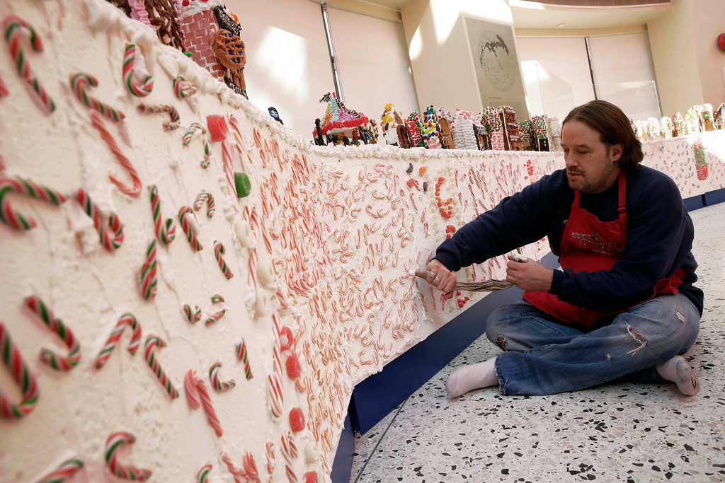 . Chef Jon Lovitch uses a pastry bag of frosting as he prepares the border for his GingerBread Lane display, at the New York Hall of Science, in the Queens borough of New York, Thursday, Nov. 13, 2014. Lovitch, a Manhattan chef who holds the Guinness record for creating the world\'s largest collection of gingerbread houses, is now going for another record, competing against himself by assembling more than 1,000 new ones. (AP Photo/Richard Drew)
