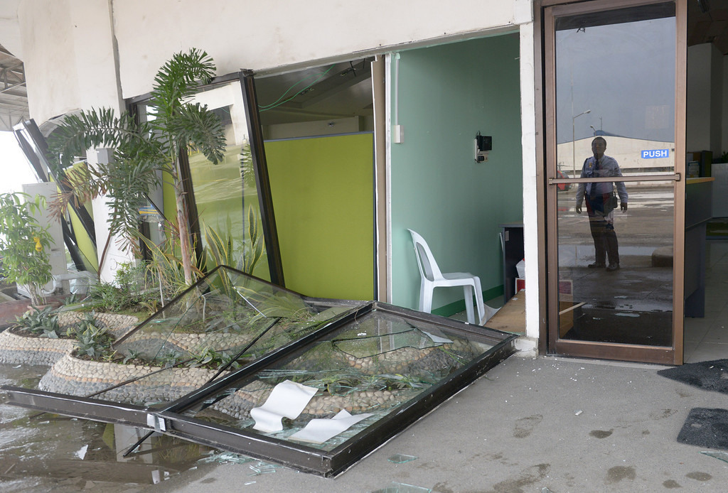 . A guard is reflected in a glass door next to a a damage government office following a 7.1-magnitude quake in Cebu on October 15, 2013.  AFP PHOTO / Jay DIRECTO/AFP/Getty Images