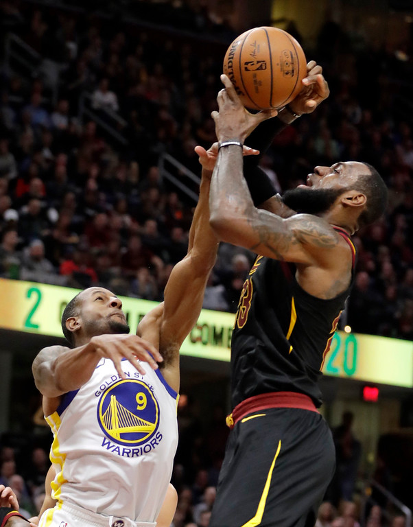 . Golden State Warriors\' Andre Iguodala, left, fouls Cleveland Cavaliers\' LeBron James in the first half of an NBA basketball game, Monday, Jan. 15, 2018, in Cleveland. (AP Photo/Tony Dejak)