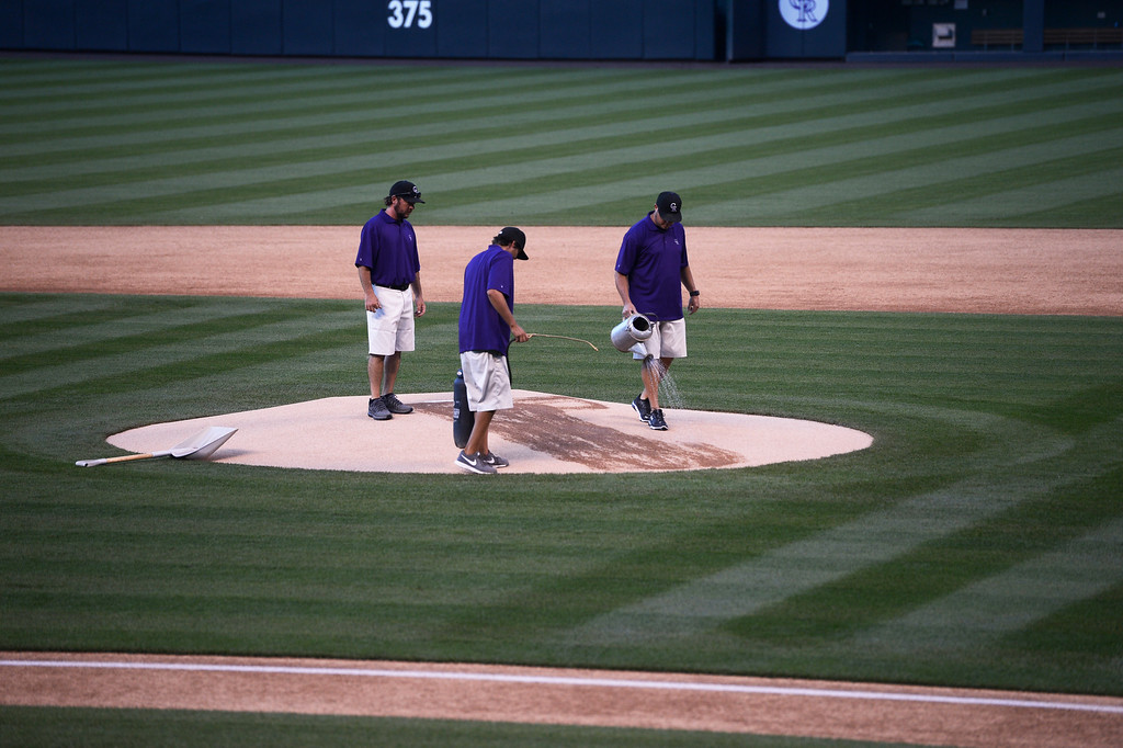 . DENVER, CO. - AUGUST 16:  Colorado Rockies grounds crew members use a watering can and a sprayer to wet down the pitchers mound at Coors Field Saturday evening, August 16, 2014. The Rockies were set to play the Cincinnati Reds but the game was cancelled due to a water main break along Blake St. out in front of Coors Field, cutting off the water supply to the stadium. (Photo By Andy Cross / The Denver Post)