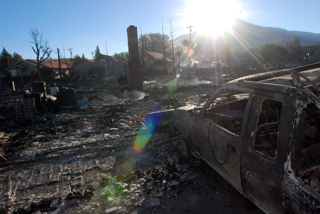 . The sun rises over Mount Shasta on Tuesday, Tuesday, Sept. 16, 2014 to illuminate the remains of a house burned in a wind-driven wildfire in Weed, Calif.  Fire crews aided by calmer winds and aircraft knocked down a wildfire Tuesday that damaged or destroyed at least 100 homes.   (AP Photo/Jeff Barnard)