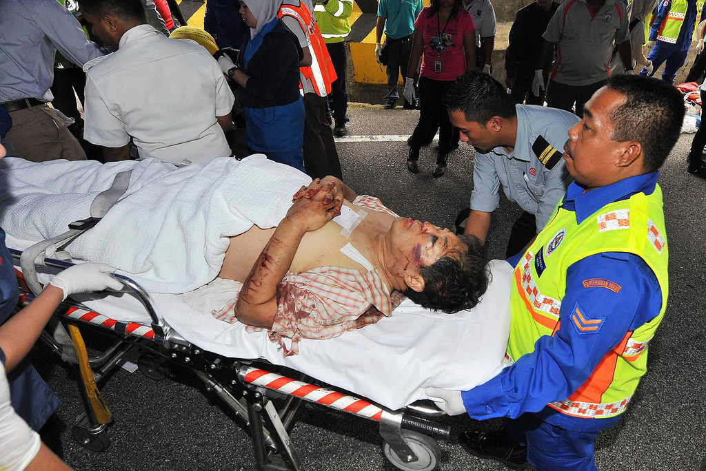 . An injured passenger is carried on a stretcher after a bus carrying tourists and local residents fell into a ravine near the Genting Highlands, Malaysia, Wednesday, Aug. 21, 2013. (AP Photo)