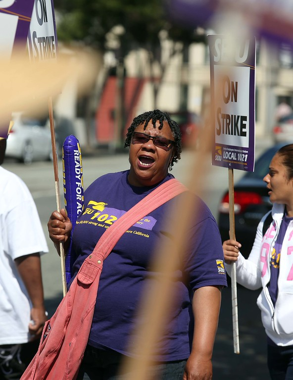 . BART employee Stephanie Keels, of Oakland, and member of the Service Employees International Union Local 1021, pickets with others in front of the Lake Merritt BART station in Oakland, Calif., on Wednesday, July 3, 2013. The BART strike is in its third day and bargaining talks will resume at 1 p.m. Wednesday. (Jane Tyska/Bay Area News Group)