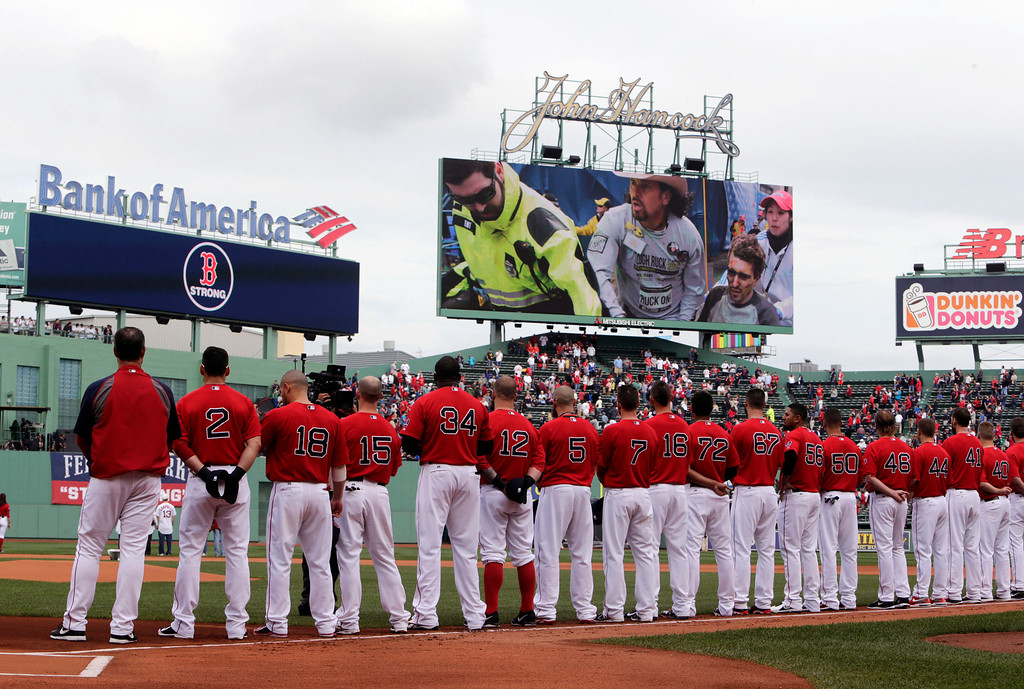 . The Boston Red Sox line the baseline as a video tribute showing Boston marathon bombing survivor Jeff Baumann, right, being assisted by Carlos Arredondo, with hat, is played before Game 1 of baseball\'s American League division series against the Tampa Bay Rays Friday, Oct. 4, 2013, in Boston. (AP Photo/Charles Krupa)