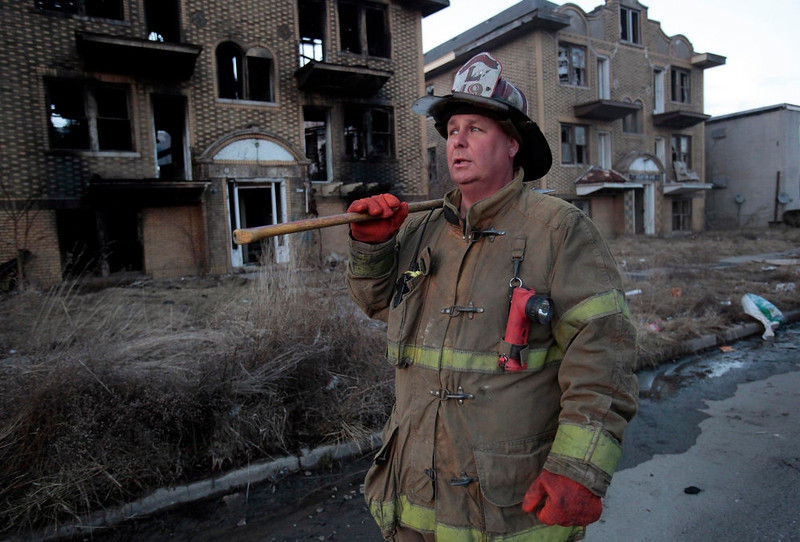 . Detroit Fire Department Lt. Ed Nadolski watches the scene as firefighters finish pouring water on a smouldering vacant apartment building that burned earlier in the day on the east side of Detroit, Michigan March 23, 2013.  When the state-imposed manager of Detroit, Kevyn Orr, begins the job on Monday he will wade into a city of crumbling neighborhoods where police fail to respond to some calls, arson fires burn out of control, and residents scour charred buildings for scrap metal to sell. Picture taken March 23, 2013.  REUTERS/ Rebecca Cook