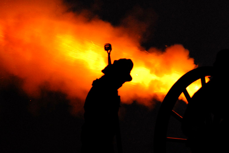 A single artillery member is silhouetted against the bright flame from a canon during a nighttime artillery demonstration at Patriots Point in Mt. Pleasant, South Carolina on Tuesday, April 12, 2011. ..The 150th Anniversary of the Firing on Ft. Sumter was commemorated with lectures, performances, demonstrations, and a living history throughout the area on James Island, Charleston, Mt. Pleasant, and Sullivan's Island during the week from April 8-14, 2011. Photo Copyright 2011 Jason Barnette