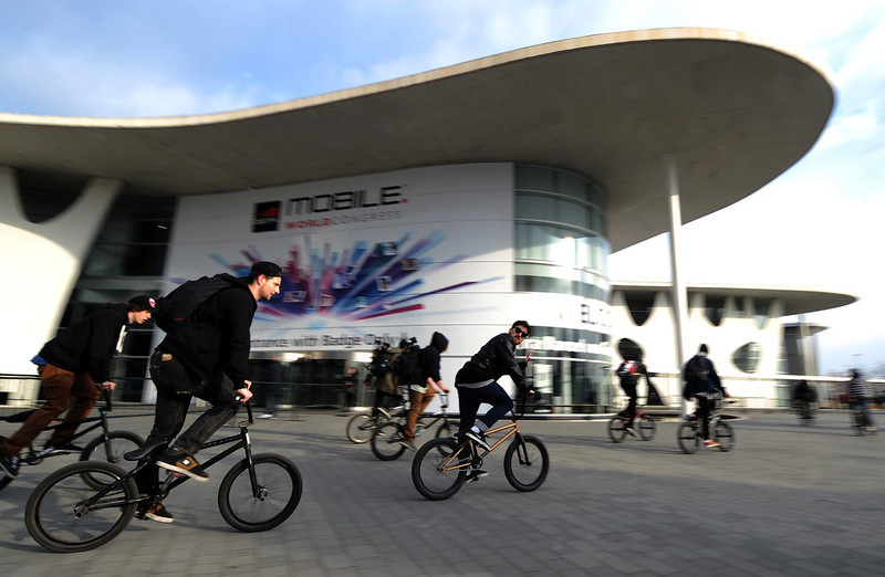 . A group of cyclists rides past the Mobile World Congress in Barcelona on February 24, 2013, a day before the start of the 2013 Mobile World Congress. The 2013 Mobile World Congress, the world\'s biggest mobile fair, is held from February 25 to February 28 in Barcelona.  LLUIS GENE/AFP/Getty Images