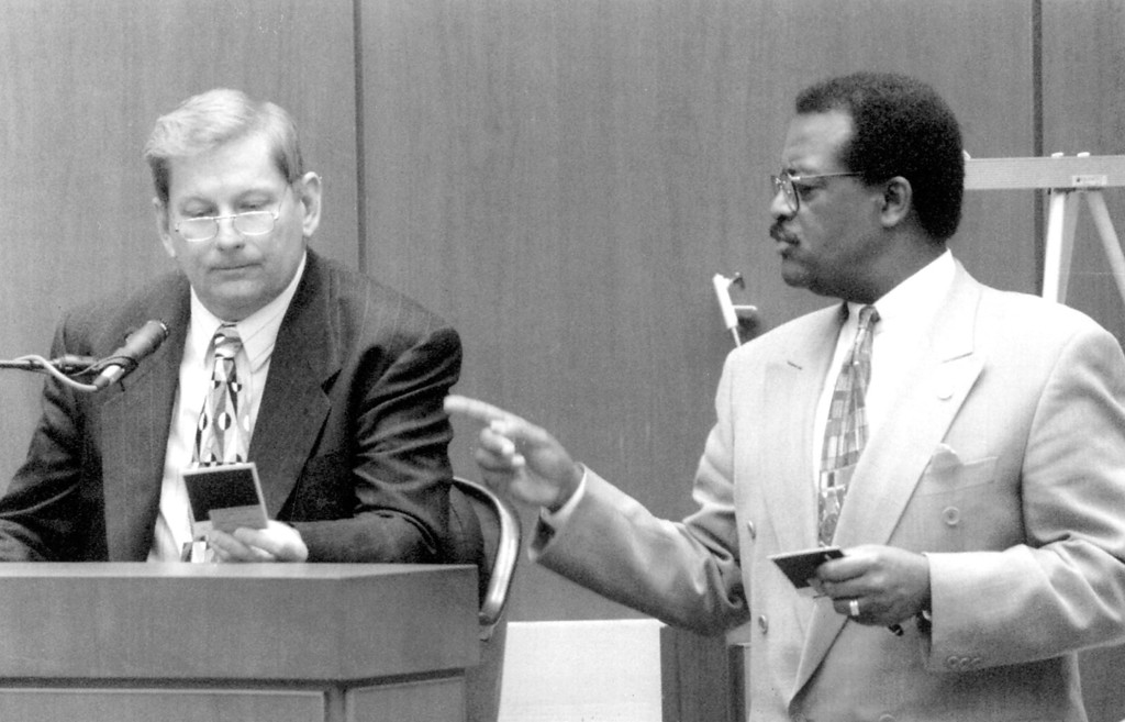 . Detective John Edwards looks at photos while defense attorney, Johnnie Cochran Jr. cross-examines.   (1995)   (Los Angeles Daily News file photo)
