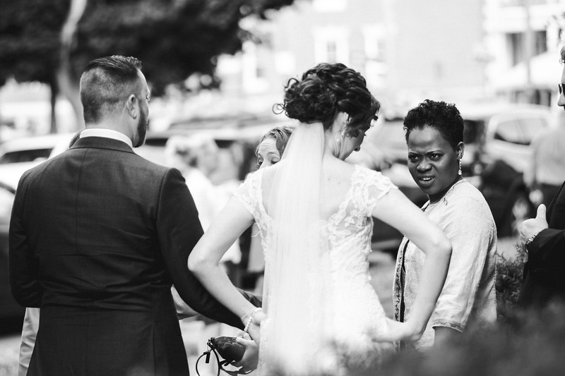 On the steps of the church, the bride has her hands on her hips as a guest looks sarcastically disgusted at the bride in a funny, ironic moment.