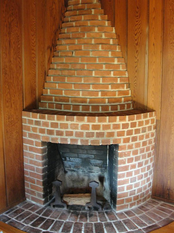 . The 1937 Berkeley Hills cabin owned by Jennifer Thomas and Rich Meyer before its 2012 remodel. The original two-sided fireplace is seen from the side facing the Dining Room. The brick was repointed and the fireplace was made structurally sound and preserved in the redesign. Gustave Carlson Design photo.