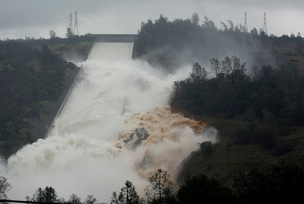". Water flows through break in the wall of the Oroville Dam spillway, Thursday, Feb. 9, 2017, in Oroville, Calif. The torrent chewed up trees and soil alongside the concrete spillway before rejoining the main channel below. Engineers don\'t know what caused what state Department of Water Resources spokesman Eric See called a ""massive\"" cave-in that is expected to keep growing until it reaches bedrock. (AP Photo/Rich Pedroncelli)"