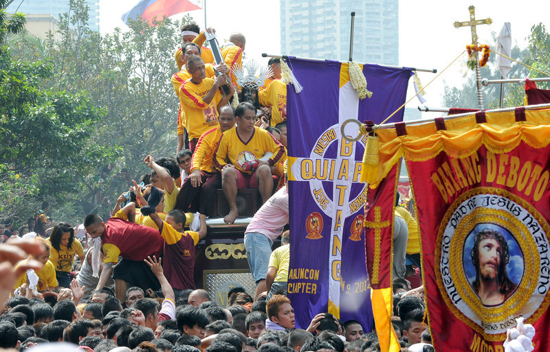. Thousands of Catholic devotees jostle for positions as they climb over one another to try to kiss the cross (C) draped on the statue of Black Nazarene during the annual procession in honor of the centuries-old icon of Jesus Christ in Manila on January 9, 2013. Masses of Catholic devotees swept through the Philippine capital on January 9 in a spectacular outpouring of passion for a centuries-old icon of Jesus Christ that many believe can perform miracles.  JAY DIRECTO/AFP/Getty Images