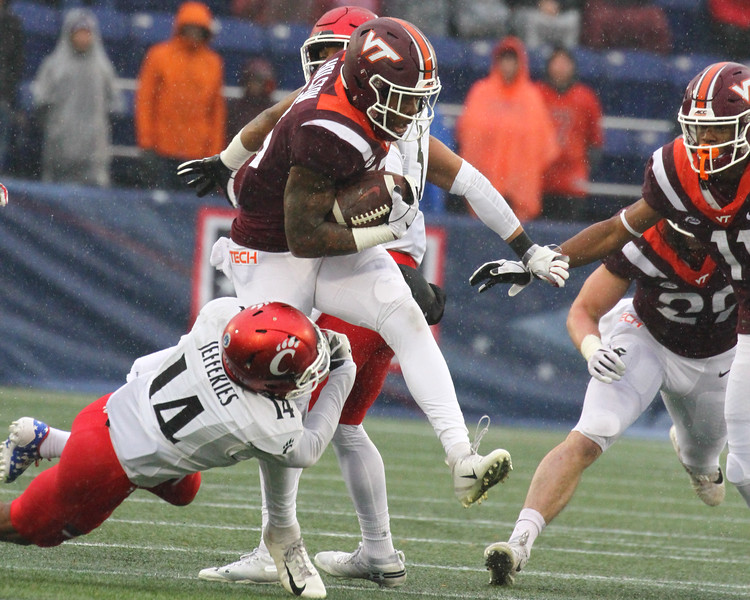 Cincinnati cornerback #14 Cam Jeffries tackles Virginia Tech runningback #13 Jalen Holston