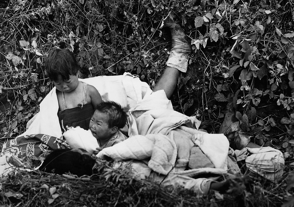 . Two children orphaned by the war are stranded in a ditch beside the body of their dead mother on the road to Pyongyang, North Korea, in Oct. 22 1950. British and Australian troops took the children to safety. (AP Photo/Max Desfor)