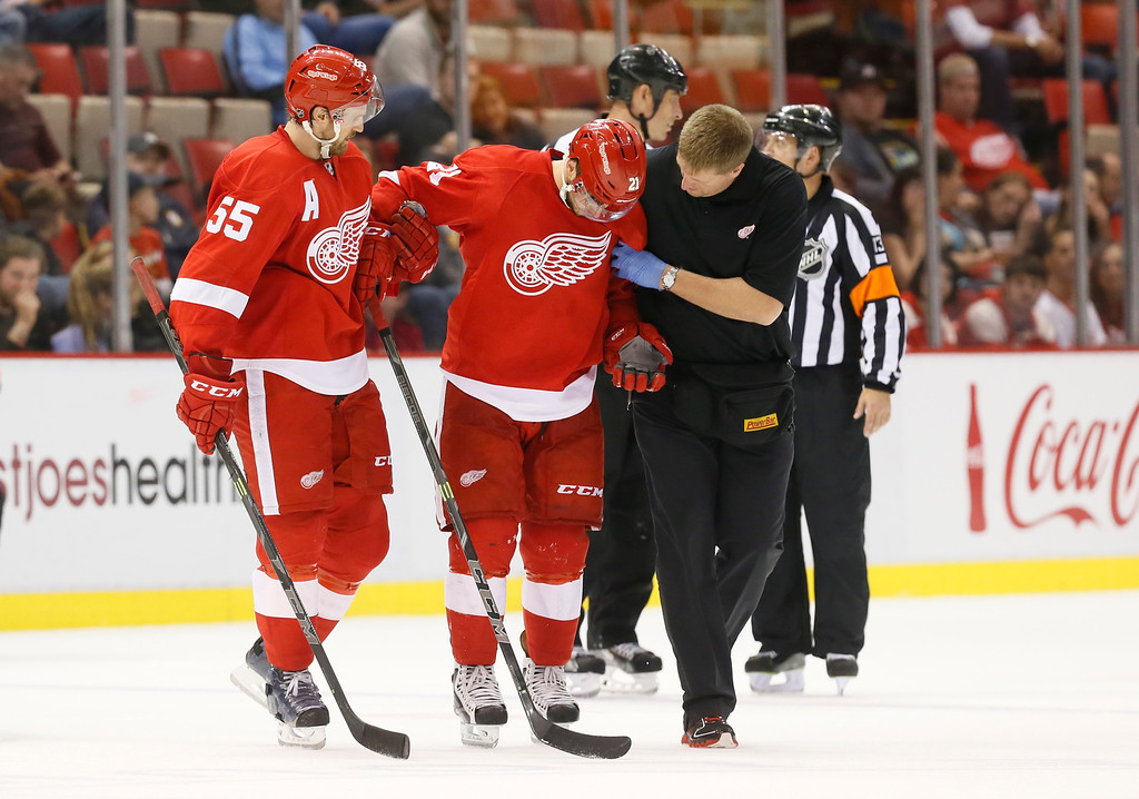 . Detroit Red Wings left wing Tomas Tatar (21), of Slovakia, is helped off the ice by Niklas Kronwall (55) and athletic trainer Piet Van Zant in the third period of a NHL preseason hockey game against the Pittsburgh Penguins in Detroit Wednesday, Oct. 1, 2014. (AP Photo/Paul Sancya)