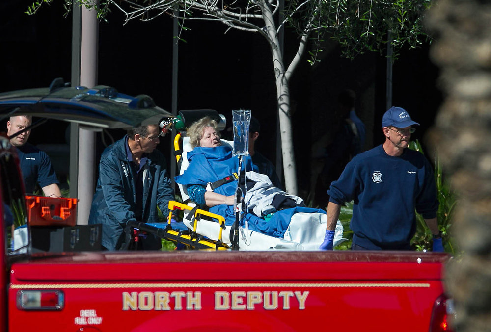 . A woman is taken to a paramedic truck from an office building where a shooter opened fire in north central Phoenix on Wednesday, Jan. 30, 2013. (AP Photo/The Arizona Republic, Michael Schennum)