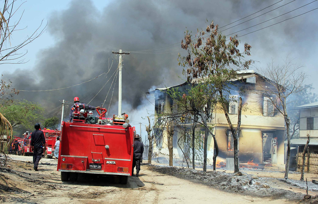 . In this Thursday, March, 21, 2013 photo, Myanmar fire fighters put out fires in a burning building following ethnic unrest between Buddhists and Muslims in Meikhtila, Mandalay division, about 550 kilometers (340 miles) north of Yangon, Myanmar.  (AP Photo)