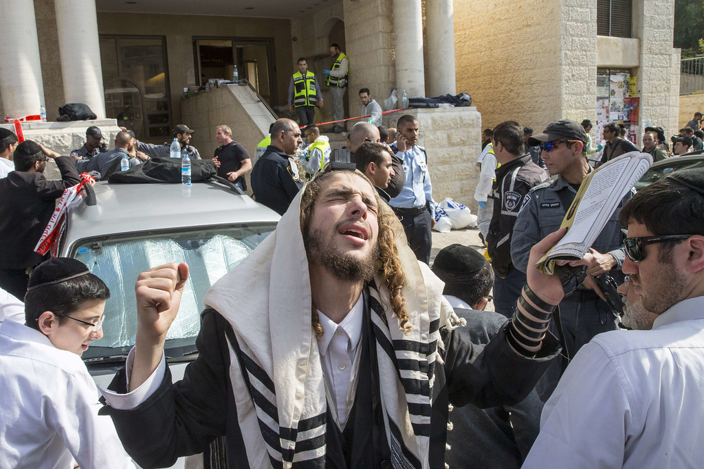 . An Ultra-orthodox jewish man prays at the scene of an attack, by two Palestinians, on Israeli worshippers at a synagogue in the ultra-Orthodox Har Nof neighborhood in Jerusalem on November 18, 2014. Two Palestinians armed with a gun and axes burst into a Jerusalem synagogue and killed four Israelis before being shot dead, in the deadliest attack in the city in years. AFP PHOTO/ JACK  GUEZ/AFP/Getty Images