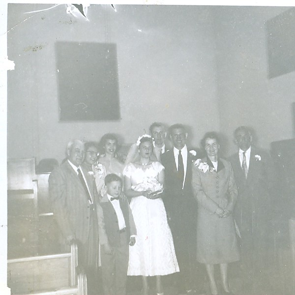 Far left: Teddy Roosevelt Wilson and Virginia Wilson (née Shute). In front of them is Michael James Wilson. In center: Cleabelle Pearce (soon to be Cleabelle Wilson, later Dobbins) with Robert Wilson. Behind them are two witnesses/friends. To the far right: Crystal Pearce (née Vaughn) and James Percy Pearce. Wedding day, Lebanon, Oregon.