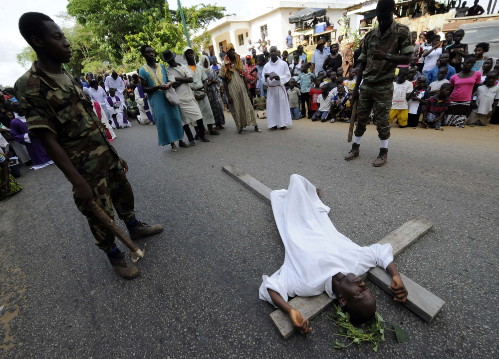 . An Ivorian man lies on a cross during a reenactment of the crucifixion of Jesus Christ as part of the Good Friday procession held by the Saint Pierre Catholic church in the district of Cocody in Abidjan on April 18, 2014. (SIA KAMBOU/AFP/Getty Images)