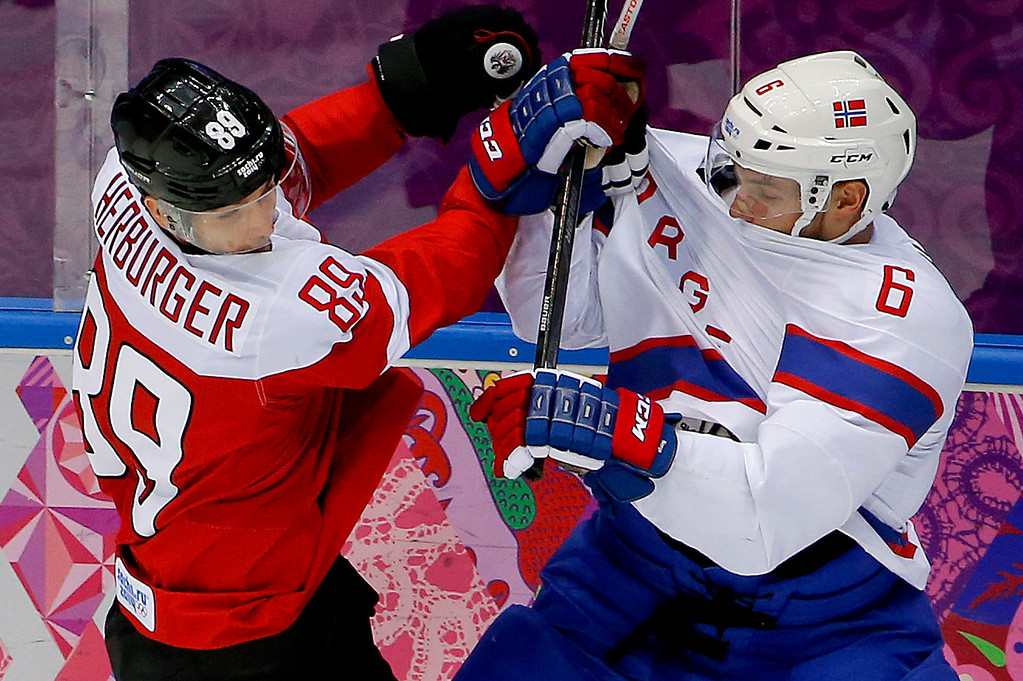 . Austria forward Raphael Herburger gets tangled up with Norway defenseman Jonas Holos in the first period of a men\'s ice hockey game at the 2014 Winter Olympics, Sunday, Feb. 16, 2014, in Sochi, Russia. (AP Photo/Julio Cortez)