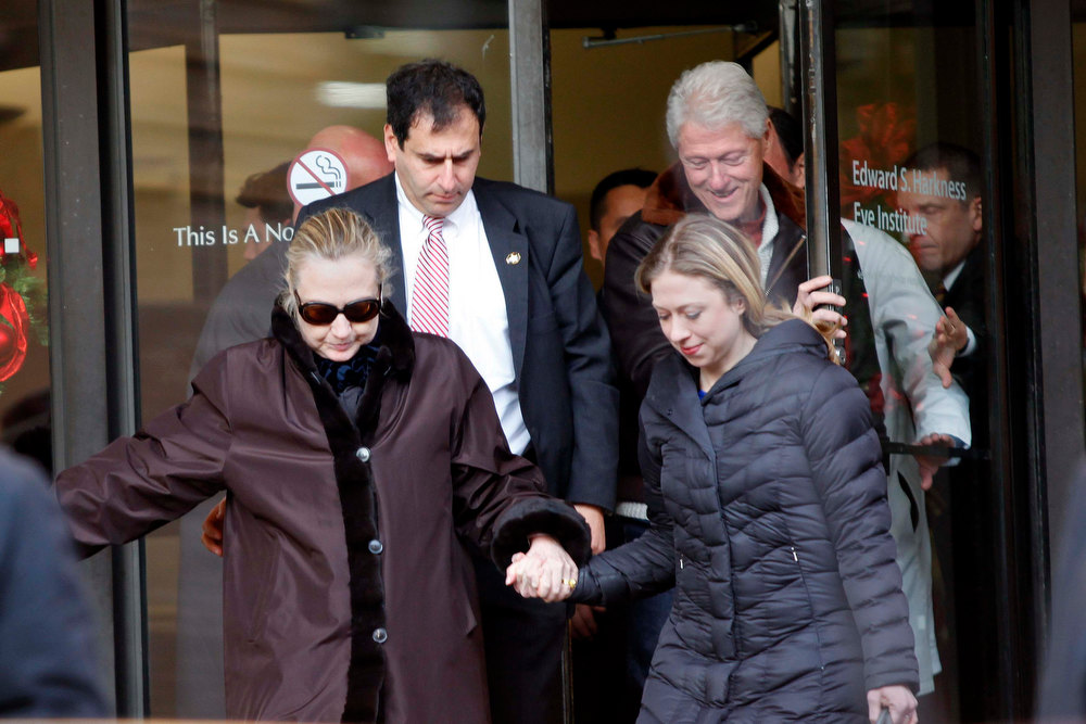 Description of . U.S. Secretary of State Hillary Clinton leaves New York Presbyterian Hospital  with husband, Bill (TOP R), and daughter, Chelsea (R), in New York, January 2, 2013. The secretary of state, who has not been seen in public since Dec. 7, was revealed on Sunday evening to be in a New York hospital under treatment for a blood clot that stemmed from a concussion she suffered in mid-December. REUTERS/Joshua Lott