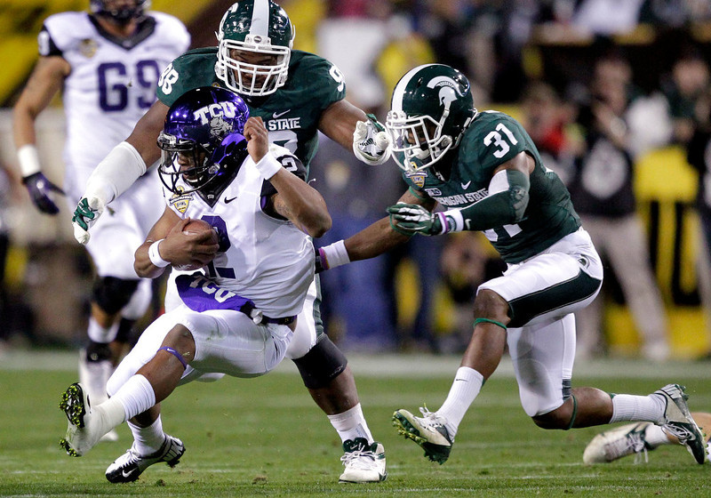 . TCU quarterback Trevone Boykin (2) is tackled by Michigan State cornerback Darqueze Dennard (31) and Jon Lewis (98) during the first half of the Buffalo Wild Wings Bowl NCAA college football game, Saturday, Dec. 29, 2012, in Tempe, Ariz. (AP Photo/Matt York)