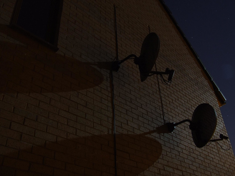 Evening sky. Satellite dishes illuminated by the moon.