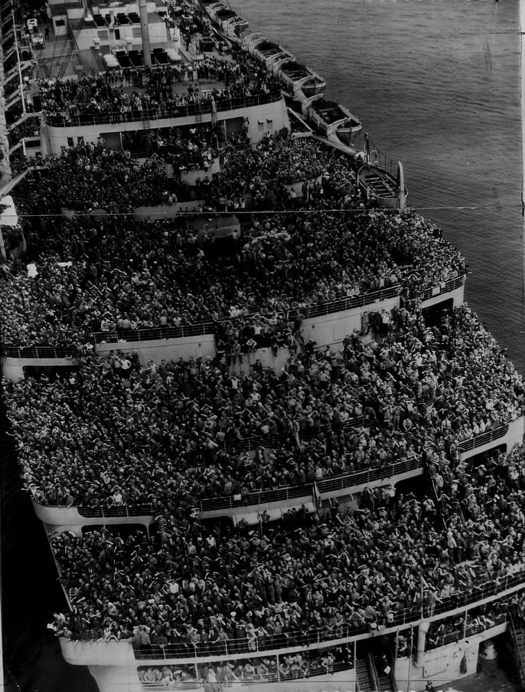 Description of . Packed Like Sardines aboard the largest liner in the world, 14,860 soldiers and sailors came home from Europe Friday as the majestic Queen Elizabeth steamed into the New York harbor to a thunderous welcome. The ship, built to carry 2,400 in peacetime, was crowded, as can be seen in this photo of her taken from a helicopter, but was a happy burden for thousands of her passengers who were on their way to furloughs with their families. Abroad were 13,658 army troops, mostly personnel of the Eighth air force and hospital units, and seven civilians.  (The Associated Press)