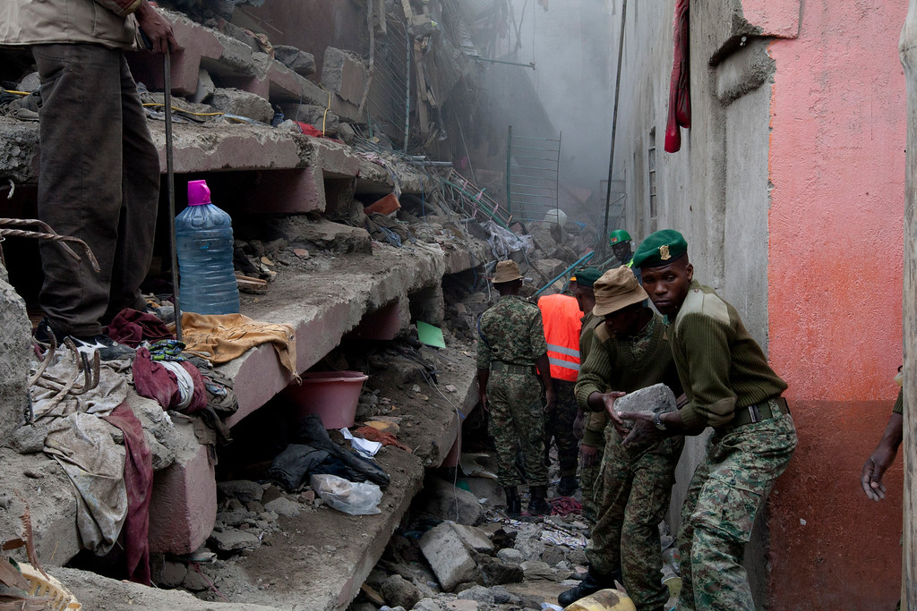 . Kenyan National Youth Service personnel remove stones with hands at the site of a building collapse in Nairobi, Kenya, Saturday, April 30, 2016. A six-story residential building in a low income area of the Kenyan capital collapsed Friday under heavy rain and flooding, trapping a number of people in the rubble, Kenyan officials said. (AP Photo/Sayyid Abdul Azim)