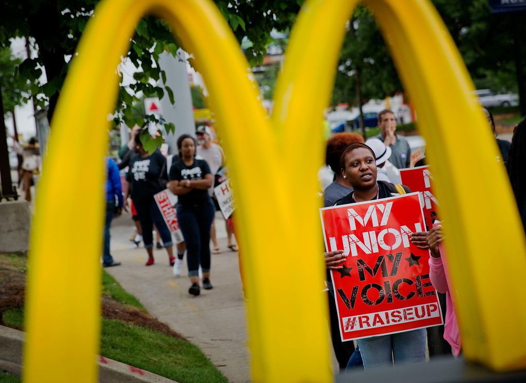 . Burger King employee Brittany Buckhannon, 24, right, demonstrates during a protest for higher wages and worker\'s unions outside a McDonald\'s restaurant, Thursday, May 15, 2014, in Atlanta.  (AP Photo/David Goldman)