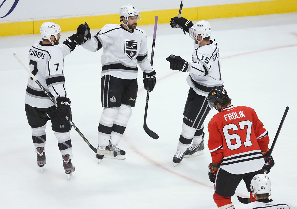 . Los Angeles Kings defenseman Rob Scuderi (7), right wing Justin Williams (14) and center Brad Richardson (15) celebrate a goal by Williams as Chicago Blackhawks center Michael Frolik (67) skates by during the first period in Game 1 of the NHL hockey Stanley Cup Western Conference finals Saturday, June 1, 2013 in Chicago. (AP Photo/Charles Rex Arbogast)