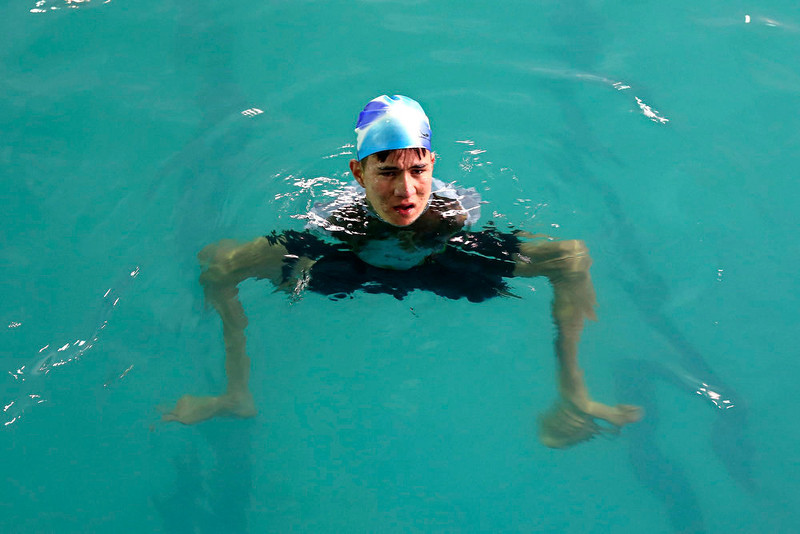 . Abbas Karimi, 14, who was born with no arms, swims at a public swimming pool in Kabul, February 12, 2013. Karimi has ambitions to earn a gold medal for his country in the world Paralympic games. If he gets the support he needs, the teenager will be the first Afghan to represent his county as a swimmer in the games next due to take place in Brazil in 2014. Picture taken February 12, 2013. REUTERS/Omar Sobhani