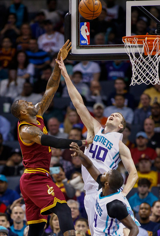 . Cleveland Cavaliers forward LeBron James, left, shoots over Charlotte Hornets forward Cody Zeller as Hornets forward Michael Kidd-Gilchrist  watches during the first half of an NBA basketball game Wednesday, Feb. 3, 2016, in Charlotte, N.C. (AP Photo/Nell Redmond)