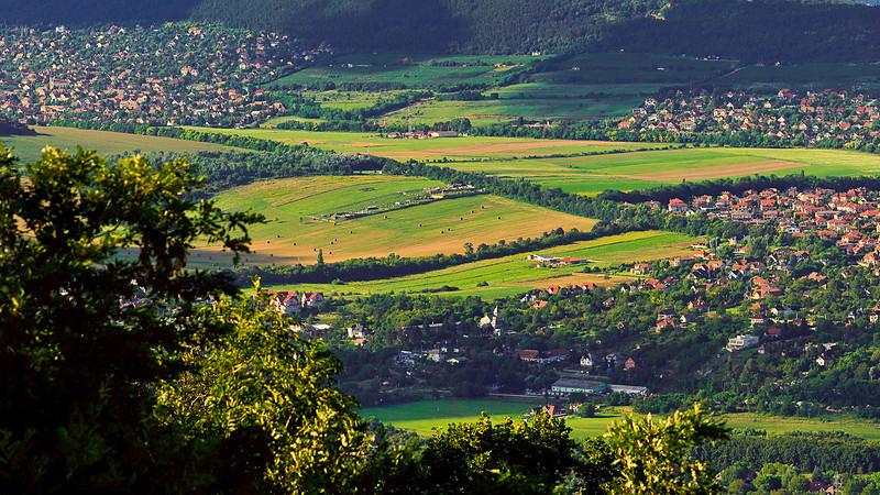 A Nagy-Kevély felé nézve a Hármashatár-hegyről. Balra fent Pilisborosjenő, alul jobbra Üröm
