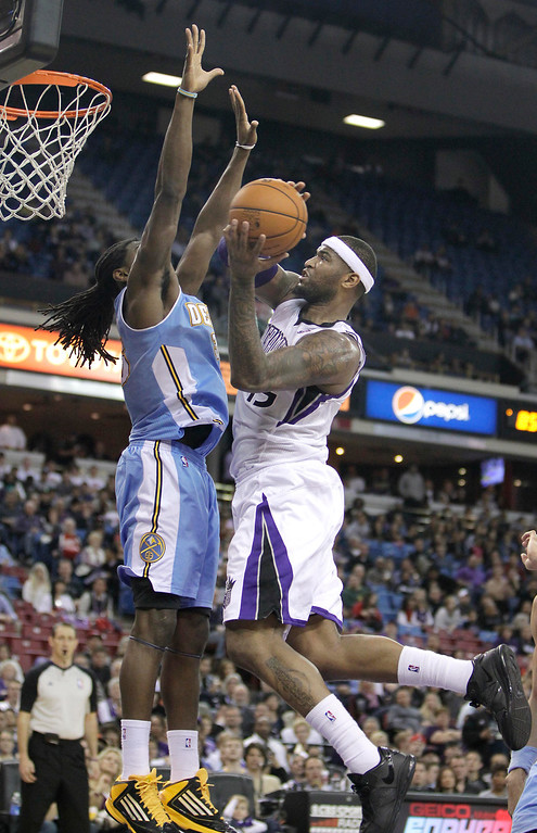 . Sacramento Kings center DeMarcus Cousins, right, goes to the basket against Denver Nuggets forward Kenneth Faried  during the fourth quarter of an NBA basketball game in Sacramento, Calif., Tuesday, March 5, 2013.  The Nuggets won 120-113.(AP Photo/Rich Pedroncelli)