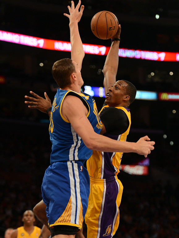 . The Dwight Howard #12 shoots as the Warriors\' Andris Biedrins #15 defends during their game at the Staples Center in Los Angeles Friday, April 12, 2013. (Hans Gutknecht/Staff Photographer)