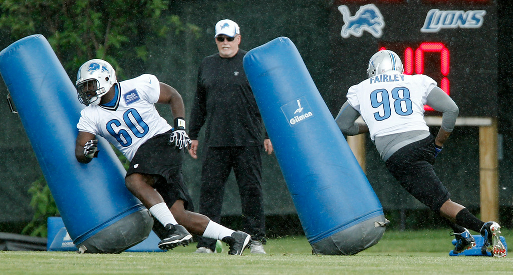 . Detroit Lions defensive tackles Gregory Hickman, left, and Nick Fairley hit the tackle dummies under the supervision of defensive line coach Jim Washburn during the final day of minicamp Thursday, June 12, 2014, in Allen Park, Mich. (AP Photo/Duane Burleson)