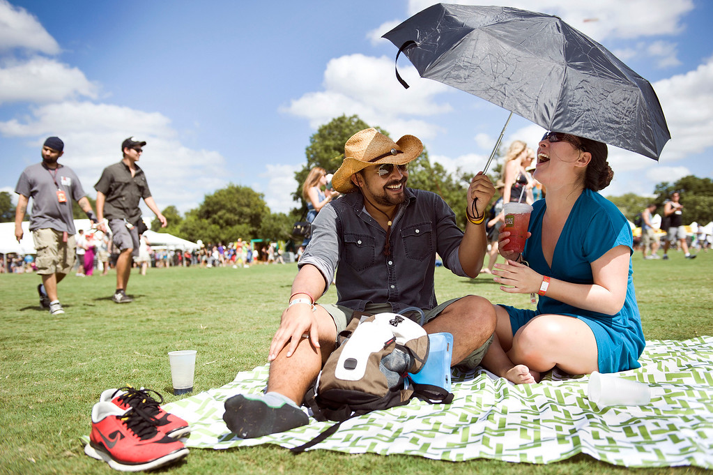 . Krys Lambiase and Margret Adams of San Antonio get some shade from the sun during the early hours of the first day of Austin City Limits festival in Austin, Texas, on Friday Oct. 4, 2013. (AP Photo/Austin American-Statesman, Erika Rich)