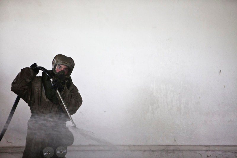 . An Israeli soldier, wearing protective gear, sprays water during a drill simulating a chemical attack in Azur, near Tel Aviv May 28, 2013. Israel continued on Tuesday with its annual home front defense exercise, launched on Monday, preparing soldiers and civilians for missile attacks. REUTERS/Nir Elias
