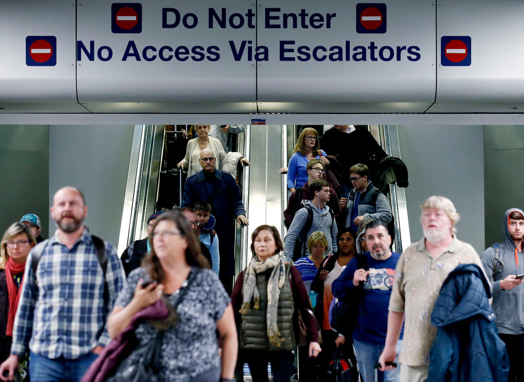. Travelers walk in Terminal 3 at O\'Hare International Airport in Chicago, Wednesday, Nov. 23, 2016. While driving remains the most popular form of transportation Thanksgiving travelers take, AAA expects just under 4 million people to fly to their holiday destinations. (AP Photo/Nam Y. Huh)