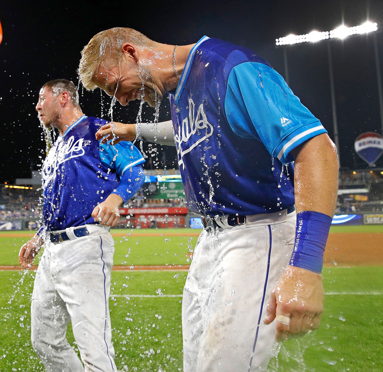 . Kansas City Royals\' Ryan O\'Hearn, left, and Hunter Dozier are doused after the team\'s baseball game against the Cleveland Indians on Friday, Aug. 24, 2018, in Kansas City, Mo. The two both had solo home runs in the ninth inning of the 5-4 Royals win. (AP Photo/Charlie Riedel)