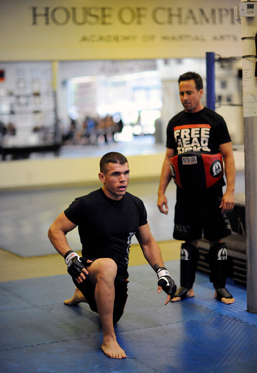 . Head instructor Mark Parra  watches UFC Fighter Eddie Mendez stretch before training at the House of Champions in Van Nuys. (Hans Gutknecht/Los Angeles Daily News)