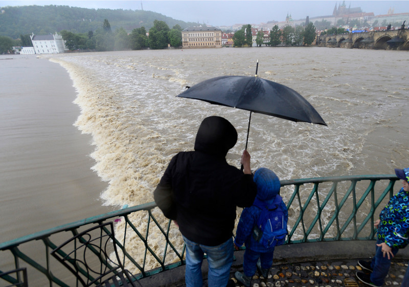 . A family watches the swollen Vltava river in the center of Prague, Czech Republic, Sunday, June 2, 2013. Heavy rainfalls cause flooding along rivers and lakes in Germany, Austria, Switzerland and the Czech Republic. (AP Photo/CTK, Roman Vondrous)