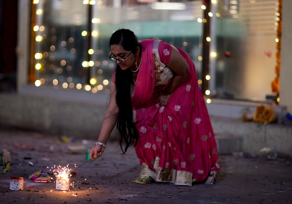 . An Indian girl plays with firecrackers to celebrate Diwali festival in Hyderabad, India, Thursday, Oct. 19, 2017. Hindus light lamps, wear new clothes, exchange sweets and gifts and pray to goddess Lakshmi during Diwali, the festival of lights. (AP Photo/Mahesh Kumar A.)