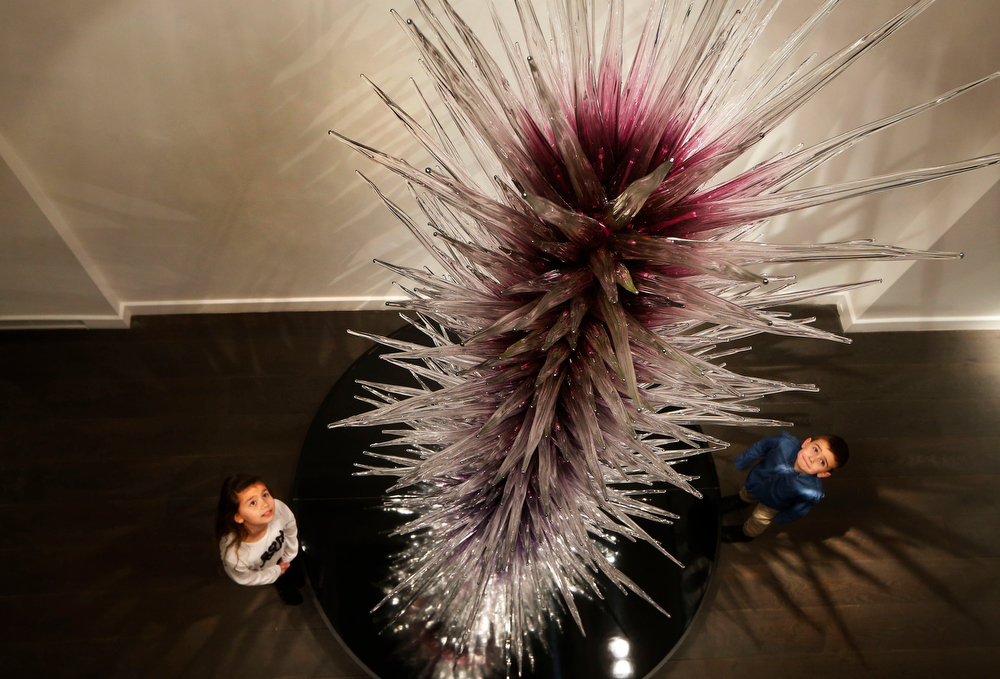 . Kristy McGuire, 8, and her brother Harry, 6, pose with a glass sculpture \'Amethyst Icicle Tower\' by U.S. artist Dale Chihuly during the launch of an exhibition of his work \'Dale Chihuly: Beyond the Object\' at the Halcyon Gallery in London, Tuesday, Feb. 4, 2014. (AP Photo/Sang Tan)