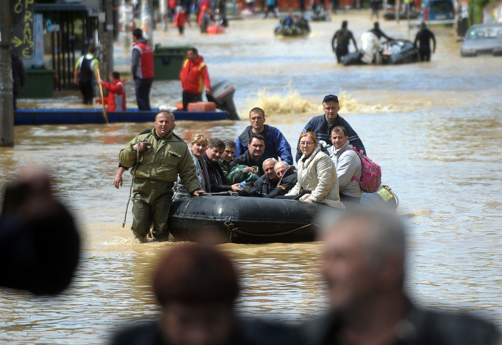 Description of . A group is evacuated on a boat over flooded streets in the town of Obrenovac, 40 kilometers west of Belgrade, on May 17, 2014. Deadly floods across Bosnia and Serbia have claimed at least 14 lives and led to the evacuation of 15,000 people after the Balkans suffered its heaviest rainfall in a century, officials said on Saturday. (ALEXA STANKOVIC/AFP/Getty Images)