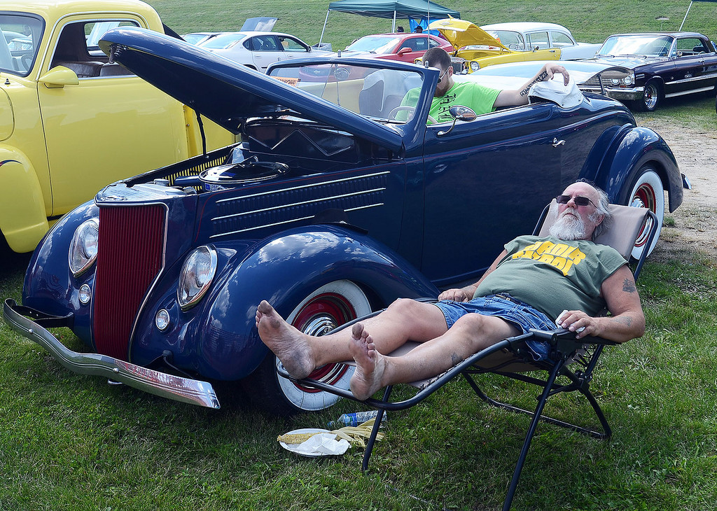 . Jim Simmons, of Davisburg, catches a little nap next to his 1936 Ford Roadster along  Woodward Avenue in Pontiac during the 2013 Woodward Dream Cruise, Saturday August 17, 2013. (Oakland Press Photo:Vaughn Gurganian)