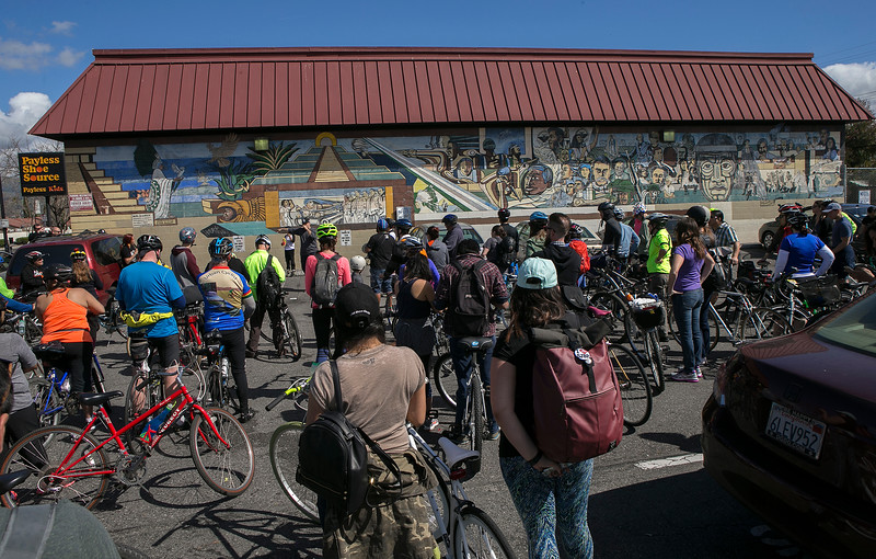 "Bikers gather in front of the ""Mural Dela Raza,"" the oldest mural in San Jose painted by Jose Meza during a bike tour of San Jose murals and ride to demonstrate a proactive response to Donald Trump's presidency in San Jose, Calif., on Saturday, March, 4, 2017. The event was sponsored by Silicon Valley De-Bug, Empire Seven Studios, and community resident Carlos Velazquez. (LiPo Ching/Bay Area News Group)"